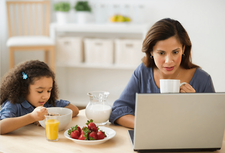 Mutter an Tisch vor ihrem Laptop. Ihr Kind isst Frühstück neben ihr.
