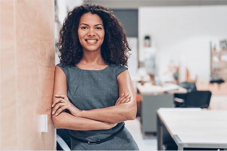 Selbstbewusste Frau, die in die Kamera lächelt. Sie hat bei ihrem Coaching gelernt, wie sie als Introvertierte Person selbstbewusst auftritt.