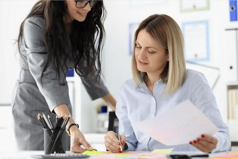 Frau übergibt Arbeit an Mitarbeiterin. Sie hat während ihrem Coaching gelernt, wie sie Aufgaben delegiert.