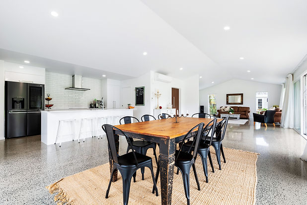 Dining and living space with high vaulted ceilings polished concrete floors and lots of natural light