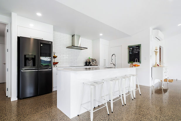 White clean Kitchen with high ceiling and polished concrete floors