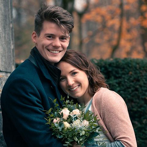 Junges Paar schmiegt sich aneinander und lächelt in die Kamera.