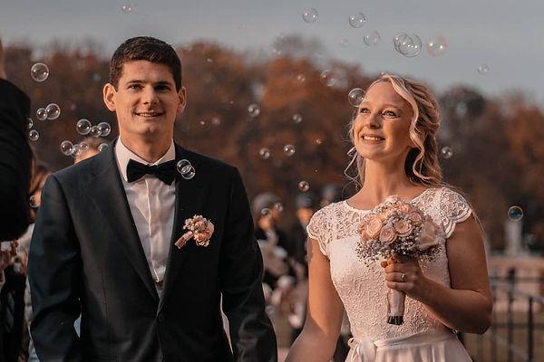 Hochzeitspaar lächelt und Seifenblasen fliegen durch die Luft.