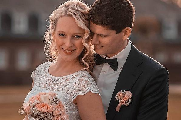 Hochzeitspaar steht aneinander geschmiegt hintereinander. Braut lächelt in die Kamera.