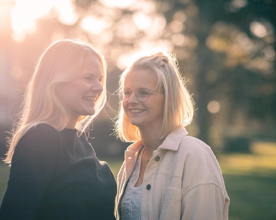 Zwei junge blonde Frauen stehen sich gegenüber und lächeln.