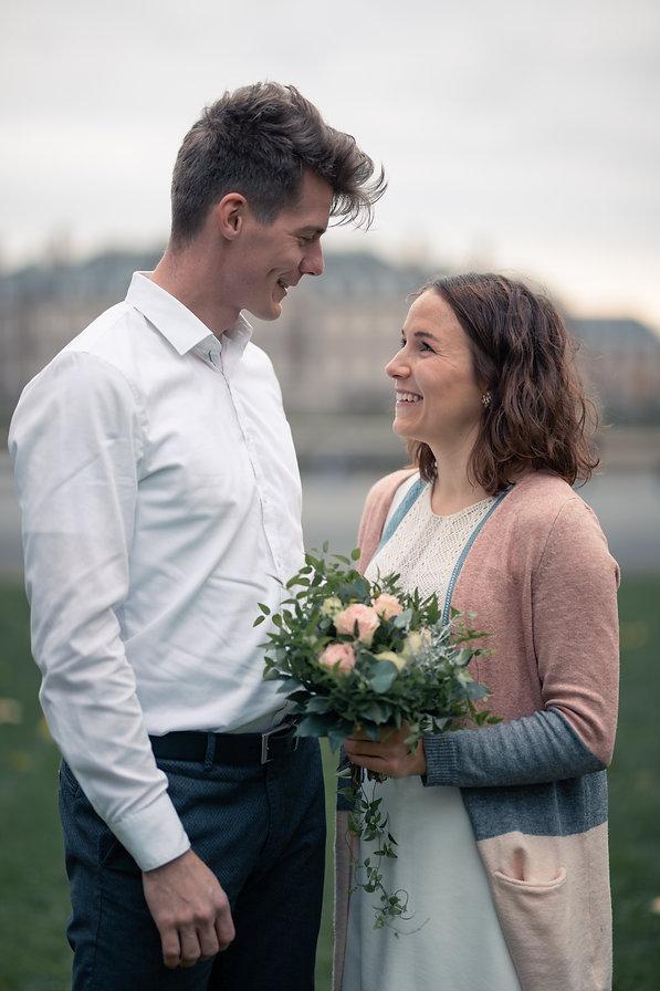 Junges Pärchen steht sich gegenüber und lächelt sich an. Die Frau hält einen kleinen Blumenstrauss in der Hand.