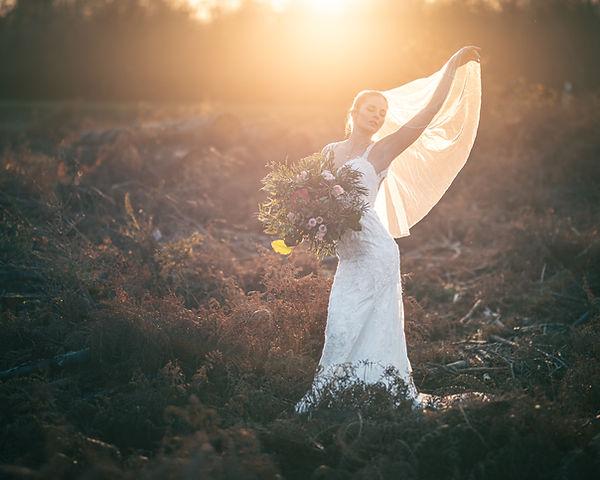 Junge Frau im Brautkleid und mit Schleier und Blumen in der Hand posiert auf einer Wiese.