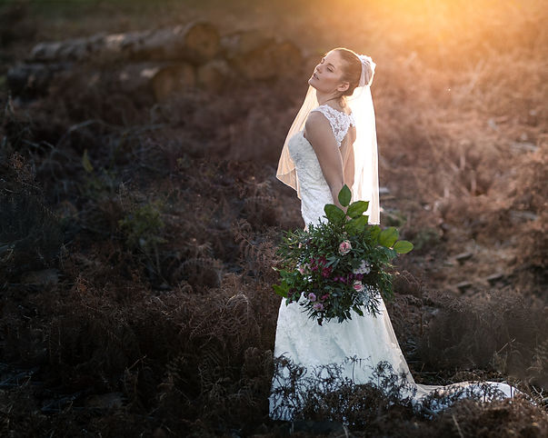 Junge Frau im Hochzeitskleid mit Blumen in der Hand steht auf einer Wiese.