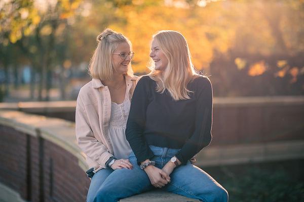 Zwei junge Mädchen sitzen auf Mauer und lächeln sich an.