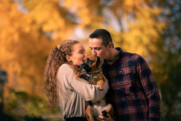 Junge Frau und junger Mann küssen Hund auf den Kopf, den sie auf dem Arm halten.