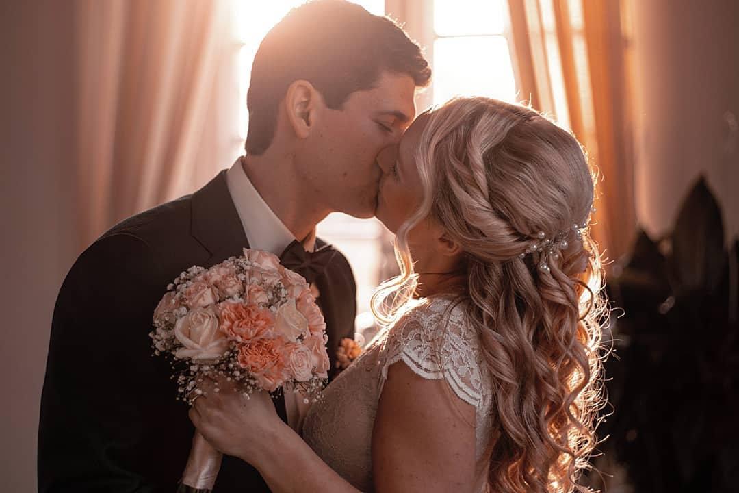 Junges Brautpaar küsst sich.