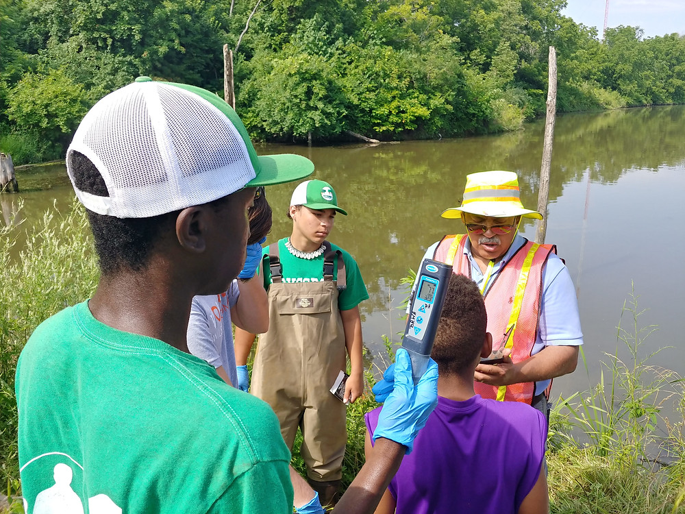 Boys Grow Volunteers test water quality at Municipal Farm. In the back, a boy stands near the water in wader overalls. Boy in front is wearing a green boys grow shirt and green and white hat. He is holding a water quality monitor with blue nitrile gloves.