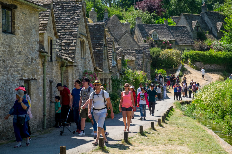 Group of tourists in the summer at  Arlington row Bibury Cotswolds