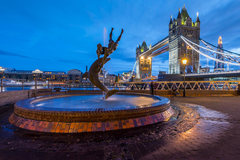 The girl and the dolphin statue near Tower Bridge at night