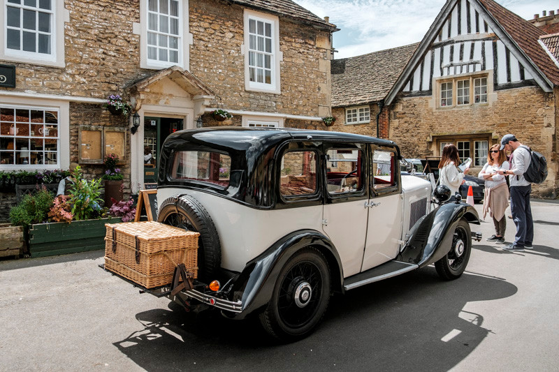 a classic car near old buildings in Cotswolds