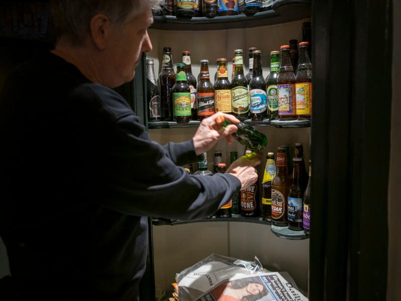 A men arranging beer bottles in a pub
