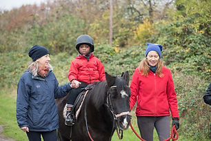 Child riding a pony being led by helpers