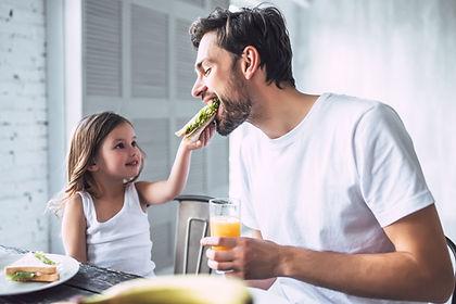Отец и дочь завтракают в новой квартире