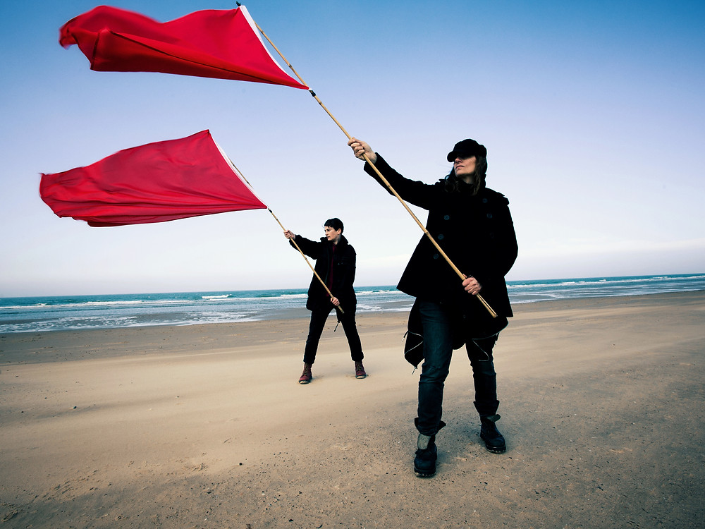 Deux Furieuses black clothes red flags beach
