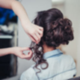 Closeup hairdresser coiffeur makes hairs