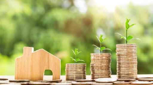Miniatura de casa de madeira com moedas aos lados, nos montes de moedas estão nascendo plantas mostrando a sustentabilidade.
