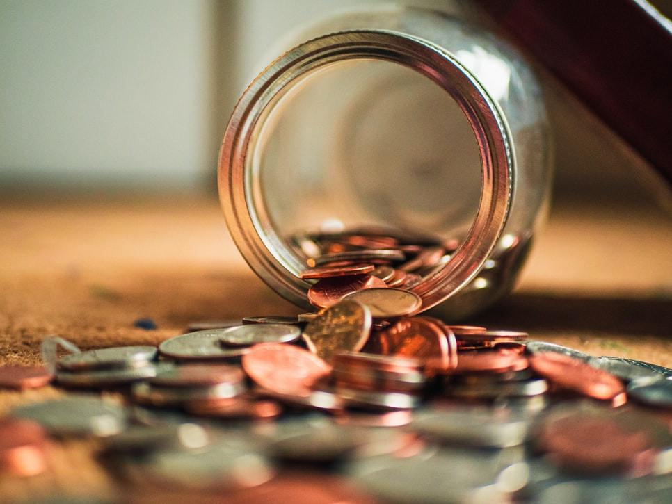 Vidro com várias moedas virado no chão