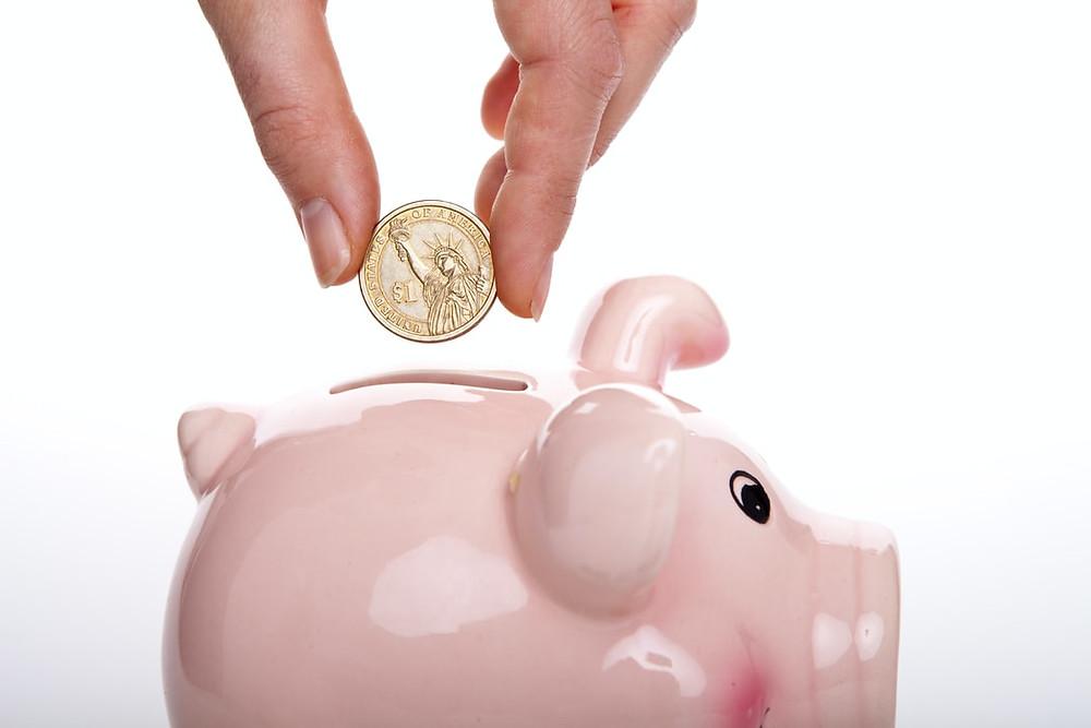 Cofrinho em formato de porco de porcelana. Há uma mão prestes a colocar uma moeda no cofre.