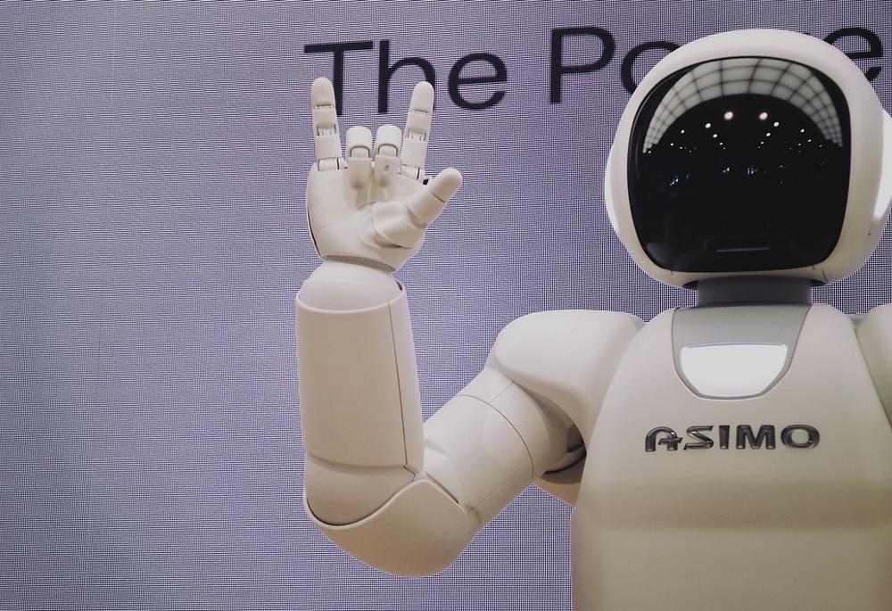 Um robô meio humanoide fazendo símbolo característico do estilo musical rock com a sua mão.