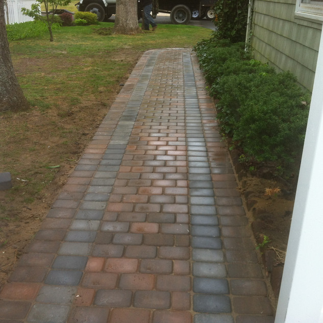 Red brick walkway with gray accent stone