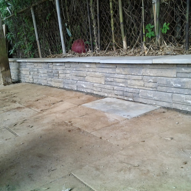 Gray stone retaining wall with seating ledge
