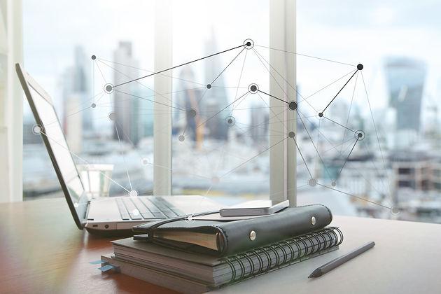 Un ordinateur portable, un agenda et un téléphone portable sur une table
