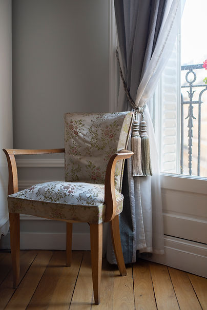 Antique wood chair upholstered in gold floral material positioned by a window in a Paris apartment
