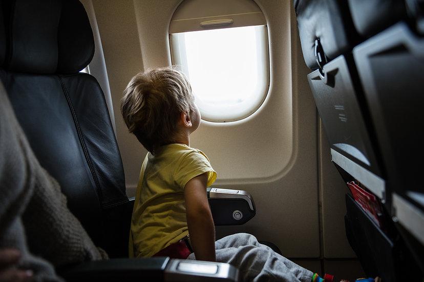 Un enfant assis dans un avion regardant par la fenêtre