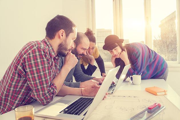 Groupe d'amis tous regardant le même écran d'ordinateur portable