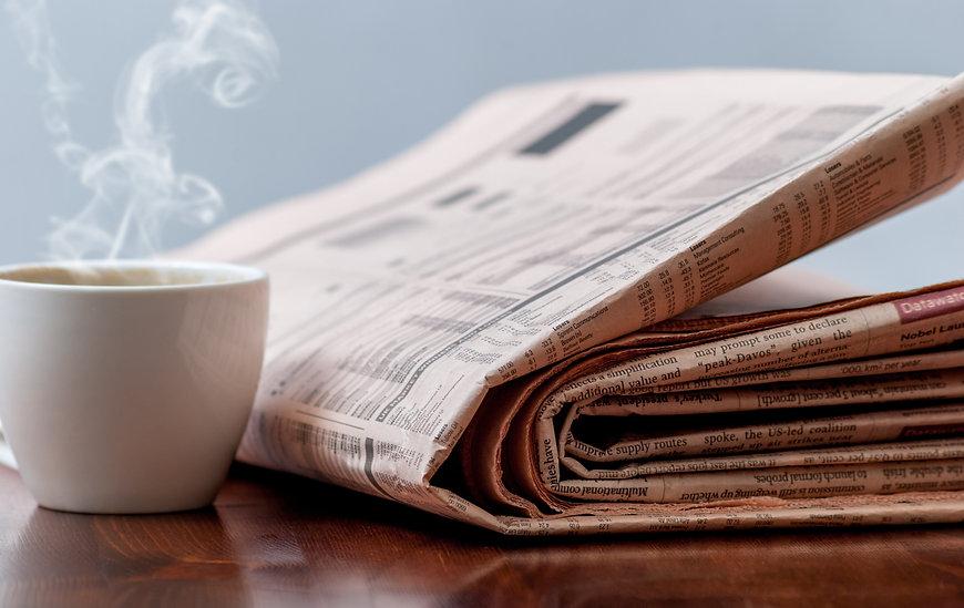un journal et une tasse de café sur une table