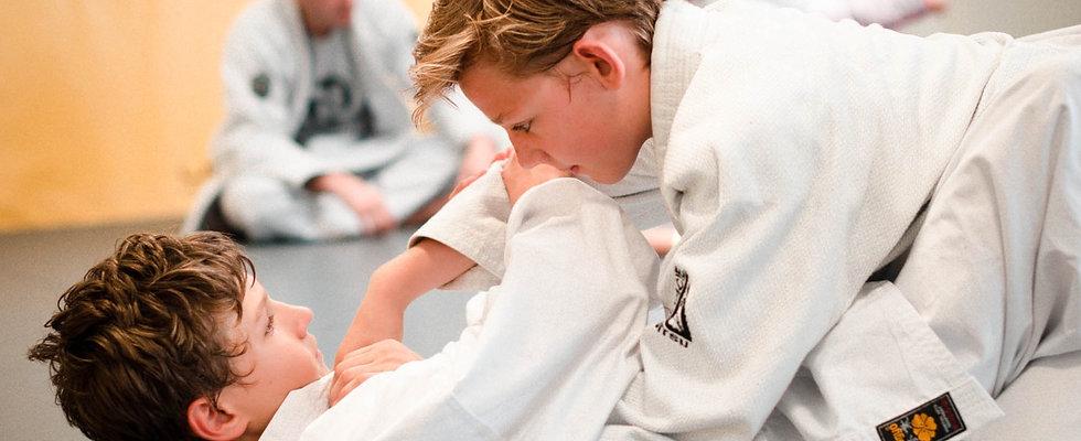 two boys sparring during a brazilian jiu jitsu class at uplay luxembourg