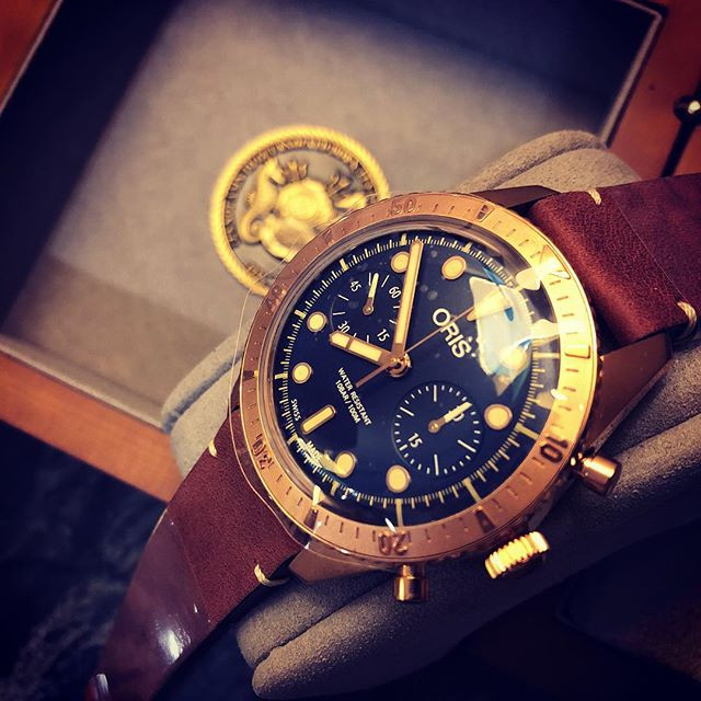 An Oris Carl Brashear with its box, strap unbent, and protective sticker still on.
