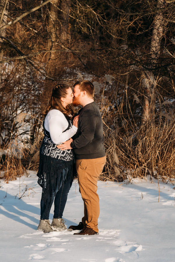 man and woman kissing at sunset on a snowy day