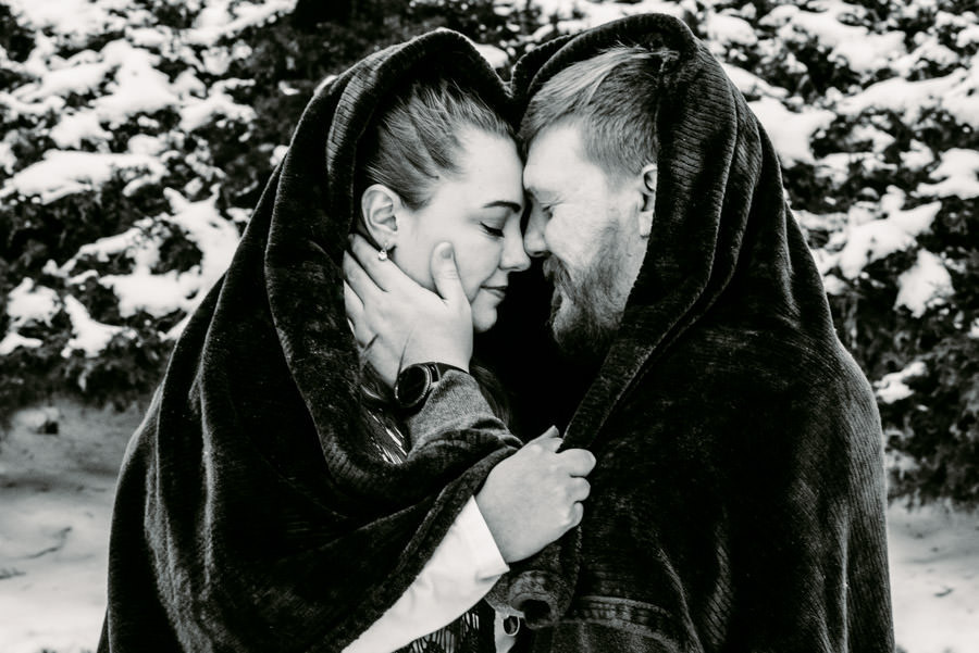 Man and woman under a red blanket outside in the snow face to face