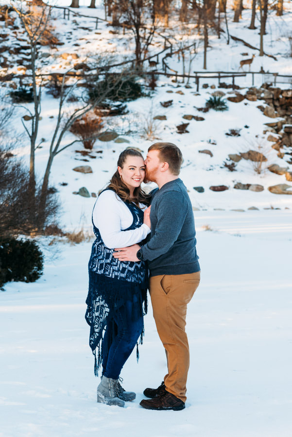 Man kissing woman's temple in a snowy park