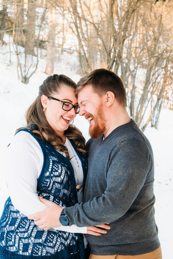 Man and woman hugging and laughing outdoors on a winter afternoon