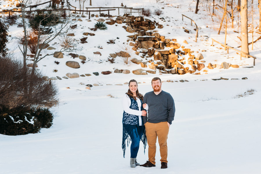 Man and woman smilins in a snow covered park