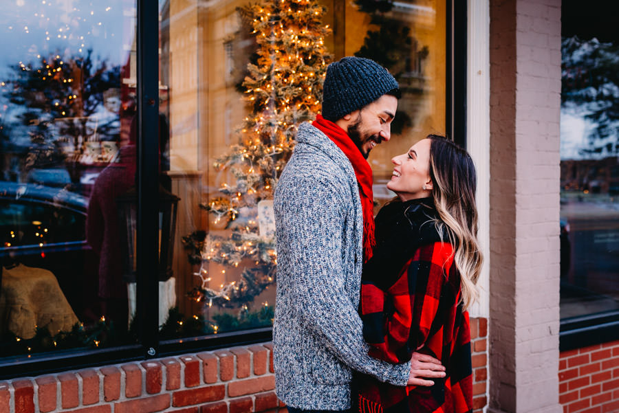 Married couple hugging outside a Christmas window display in Hillsdale Michigan