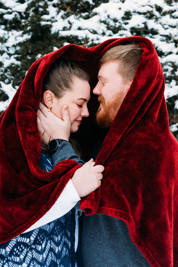 Man and woman outside in the snow under a red blanket snuggling