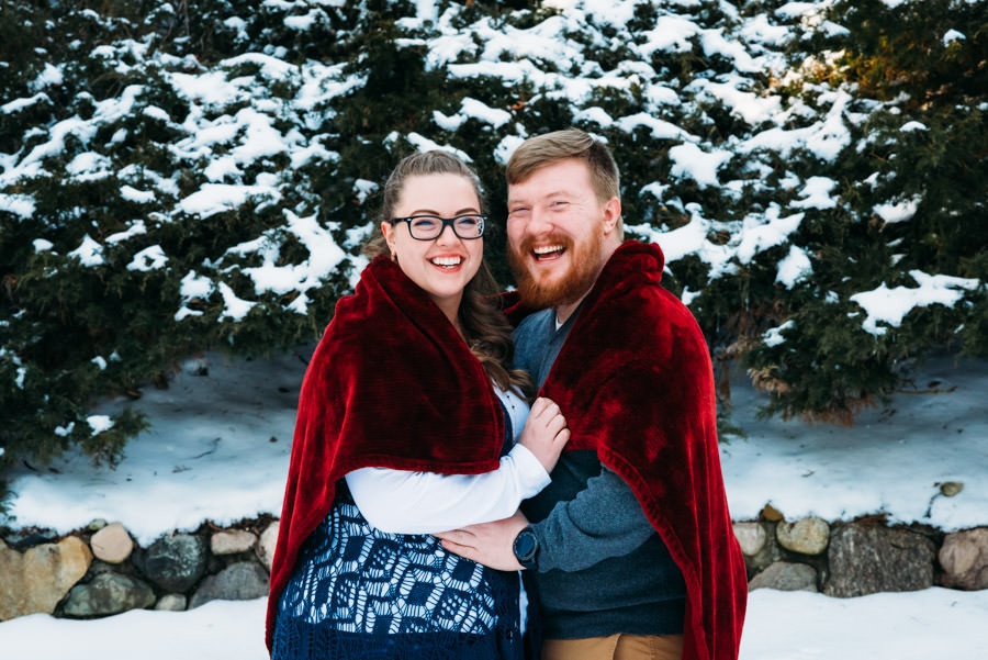 woman and man wrapped in a red blanket outside in a park in the winter