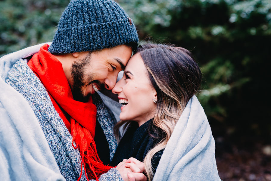 Engagement photo of man and woman with foreheads together laughing