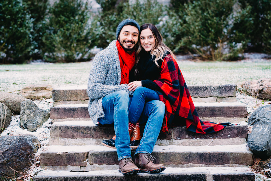 Married couple sitting on the step in the winter at Hillsdale College