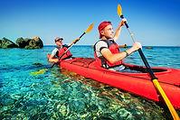 Two men paddle a kayak on the sea. Kayak