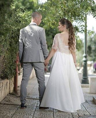 A כלה לובשת שמלת כלה בתפירה אישית עם גב פתוח וחצאית