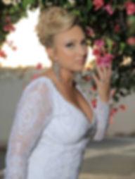 כלה לובשת שמלת כלה בתפירה אישית עם תחרה, שרוולים ארוכים ומחשוף